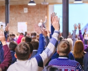 hands raised in large classroom